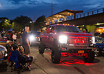 Bellmore, New York, USA. 12th July 2015. People watch as a custom GMC dually lifted diesel truck that is red underlit drives past to leave the Friday Night Car Show held at the Bellmore Long Island Railroad Station Parking Lot. Hundreds of classic, antique, and custom cars were on view at the free weekly show, sponsored by the Chamber of Commerce of the Bellmores.