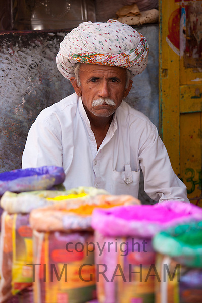 Indian man selling powder paint colours for Holi festival on sale at Katala Bazar in Jodhpur, Rajasthan, Northern India