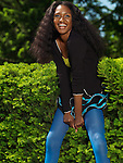 Laughing young stylish woman in colorful clothes in a park