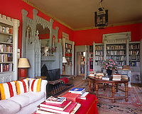 In this bright red living room a gothic overmantel complete with mirror is matched with castellated  bookcases