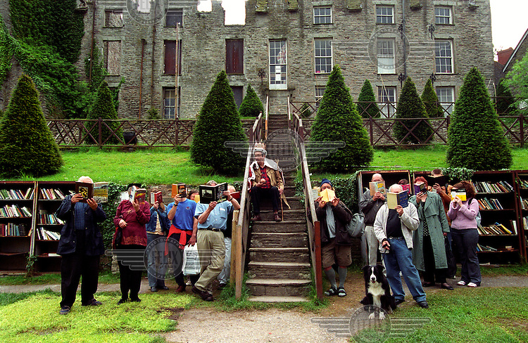 The King of Hay outside the castle together with his Book Terrorists. Because of the shortage of balaclavas the terrorists are hiding their identities behind books.