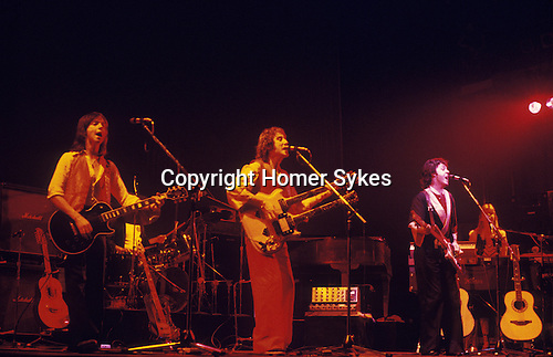 "Paul and Linda McCartney Wings Tour 1975. Wings on stage, Jimmy McCulloch, Denny Laine, paul and Linda, drummer Joe English, Bristol, England.. The photographs from this set were taken in 1975. I was on tour with them for a children's ""Fact Book"". This book was called, The Facts about a Pop Group Featuring Wings. Introduced by Paul McCartney, published by G.Whizzard. They had recently recorded albums, Wildlife, Red Rose Speedway, Band on the Run and Venus and Mars. I believe it was the English leg of Wings Over the World tour. But as I recall they were promoting,  Band on the Run and Venus and Mars in particular."