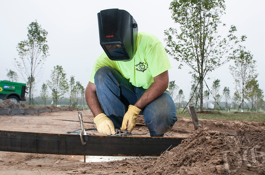 STAFF PHOTO ANTHONY REYES &bull; @NWATONYR<br /> Ben Sarratt, with Diamond C Construction of Gentry, welds forms to rebar set in the ground Tuesday, Sept. 16, 2014 for the Legacy Orchards project at Orchard Park in Bentonville. After the forms are built the crew will put a layer of gravel and then a layer of decorative red aggregate between the rows of maple trees. The project is set to finish this year.