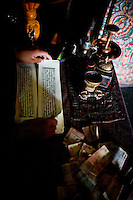 Chamba, a 19 year old monk flips his notes as he repetitiously chants prayers while beating a drum in the Gonkhang of Thiksay Monastery, Leh, Ladakh, Jammu & Kashmir, India, on the morning of 1st June 2009. The 500 year old Gonkhang is a dark and solemn room that houses ferocious protecters of the dieties. The designated monk that chants in this room does so for 6 hours per day, every day for a full year. Thiksay, founded in the 15th century, sits on a hill 19 km southeast of Leh town, and houses approximately 100 monks.  Photo by Suzanne Lee