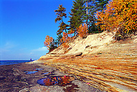A MAN WALKS ALONG A BEACH NEAR THE MOSQUITO RIVER IN PICTURED ROCKS NATIONAL LAKESHORE NEAR MUNISING MICHIGAN.
