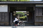 A schoolgirl cycles past a museum that was once a samurai's residence in Shiomi Nawate district near Matsue Castle in Matsue City, Shimane Prefecture, Japan on 26 June 2011.  Photographer: Robert Gilhooly