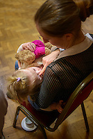 A mother breastfeeding her toddler at a conference.<br /> <br /> Image from the breastfeeding collection of the &quot;We Do It In Public&quot; documentary photography picture library project: <br />  www.breastfeedinginpublic.co.uk<br /> <br /> <br /> Middlesex, England, UK<br /> 2016<br /> <br /> &copy; Paul Carter / wdiip.co.uk