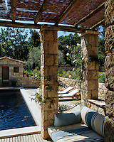 A covered arbour made from local limestone is situated at one end of a black-lined swimming pool