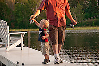 A young boy fishes with his father on the Michigamme River at the Republic Island Cottage near Republic Michigan.
