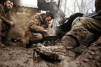 """UKRAINE, 02.2016, Oblast Donetsk. Ukrainian-Russian conflict concerning Eastern Ukraine / Foreign volunteers (""""Task Force Pluto"""") fighting with the far-right militia Pravyi Sektor against the Russian-backed separatists: Ben and Alex from Austria prepare a meal on the camp fire in their muddy trench at the Donetsk frontline. © Timo Vogt/EST&OST"""