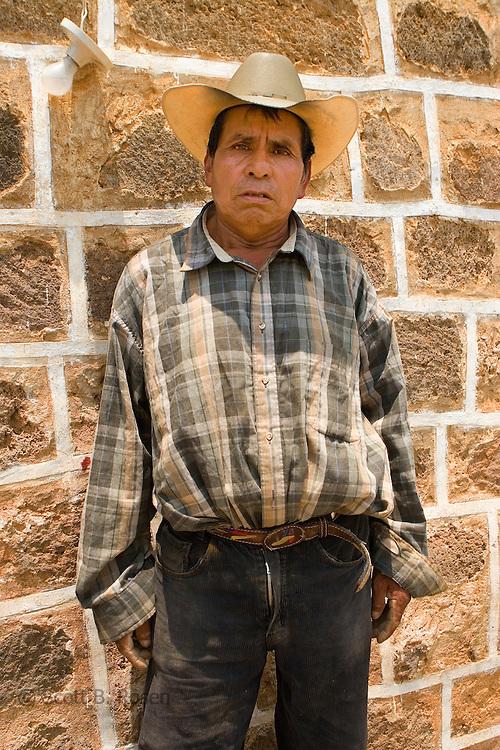 Portrait of Guatemalan man with cowboy hat in front of church wall in San Juan La Laguna, Lake Atitlan, Guatemala