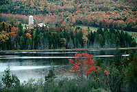 Joes pond in fall with farm and silo tucked in the hills across the lake in fall color. Vermont USA