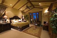 Luxurious master suite with vaulted ceiling and elegant furniture is seen at night