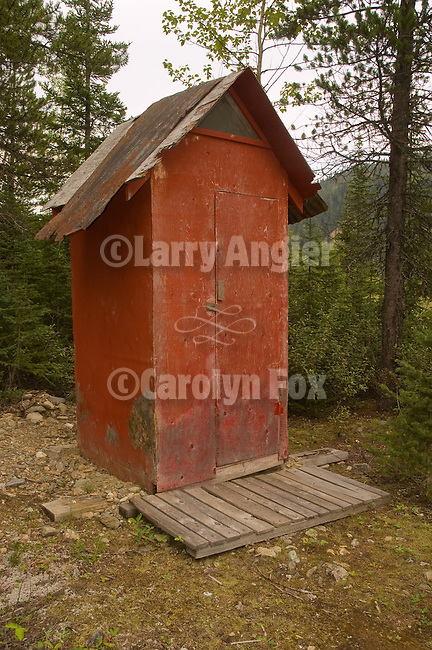 Tall red wooden outhouse in the forest of the Cariboo Range, British Columbia