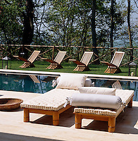 Teak sun-loungers and deck chairs surround the swimming pool