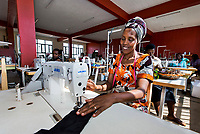 Africa, Rwanda, Kigali. Women for Women project. Women at the Gahaya Links Factory where they make clothing, jewelry & baskets for export. Mary Kantengwa (in turban), learning to sew on industrial sewing machines. With teacher, Innocent Rwamacyo (man).