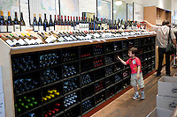 A little boy looks through the wine bottles on a rack at Chambers Street Wines in New York, NY, USA, 22 May 2009. The store specializes in naturally made wines from artisanal small producers and has received a Slow Food NYC Snail of Approval.