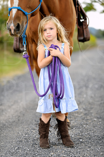 Little blonde girl posing with her big horse on a country lane, confident pose with steady gaze, blue sun dress and tall boots.