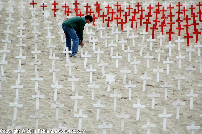 Chris McCourmack, a Veterans for Peace volunteer, erects crosses for the Veterans Day memorial at Arlington West on Friday, November 11, 2011.