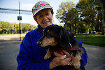 Older woman holding long haired dachshund dog at the baseball field, Central Park, NYC