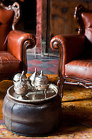 Detail of antique Moroccan silverware on a traditional leather pouf in the living room of The Red Apartment at the Riad Dar Darma