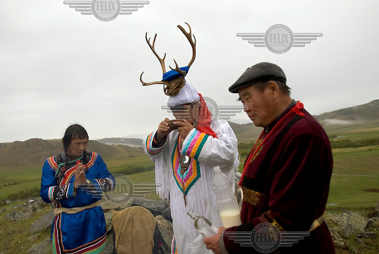 A Buryat shaman drinks kumiss (fermented mare's milk) during a ceremony atop a sacred hill near Lake Baikal. The holiday, which occurs once every four or five years, celebrates Buryat culture and Buryat communities from all over Lake Baikal come to participate in sports, music and cultural competitions.