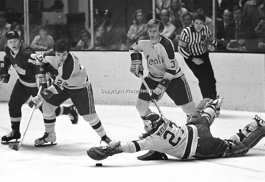Seals Paul Shmyr and Ernie Hicke move Butch Goring away as Gilles Meloche glove the puck. (photo/Ron Riesterer)