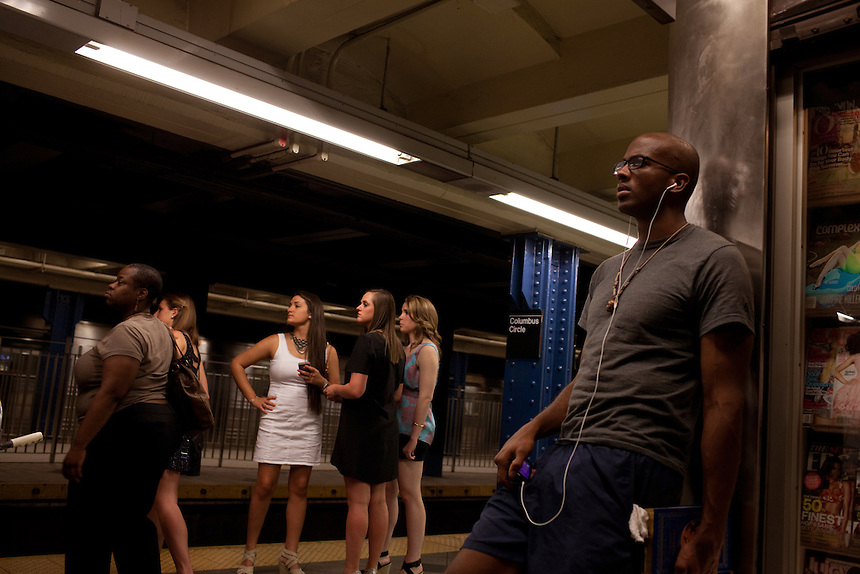 Commuters wait for the A train at the Columbus Circle subway stop in New York on June 23, 2012.