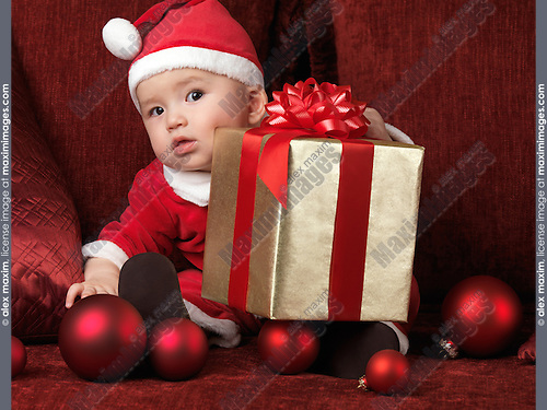 Six month old baby boy in Santa costume with a Christmas present on his lap