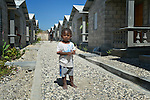 """A child stands amid houses in a model resettlement village constructed by the Lutheran World Federation in Gressier, Haiti. The settlement houses 150 families who were left homeless by the 2010 earthquake, and represents an intentional effort to """"build back better,"""" creating a sustainable and democratic community."""