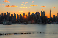 The rising sun shines through the buildings of the Manhattan skyline a few minutes after sunrise as viewed over the Hudson River looking east from New Jersey.