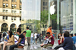 NYC, New York, U.S.  21st May 2013. Clusters of people relax in front of the Apple store on 5th Avenue, with the large white Apple logo suspended in the 32-foot structural glass cube entrance, at 767 Fifth Avenue between 58th and 59th Streets, during a pleasant spring day, with a high of 86ºF/32ºC in Manhattan.