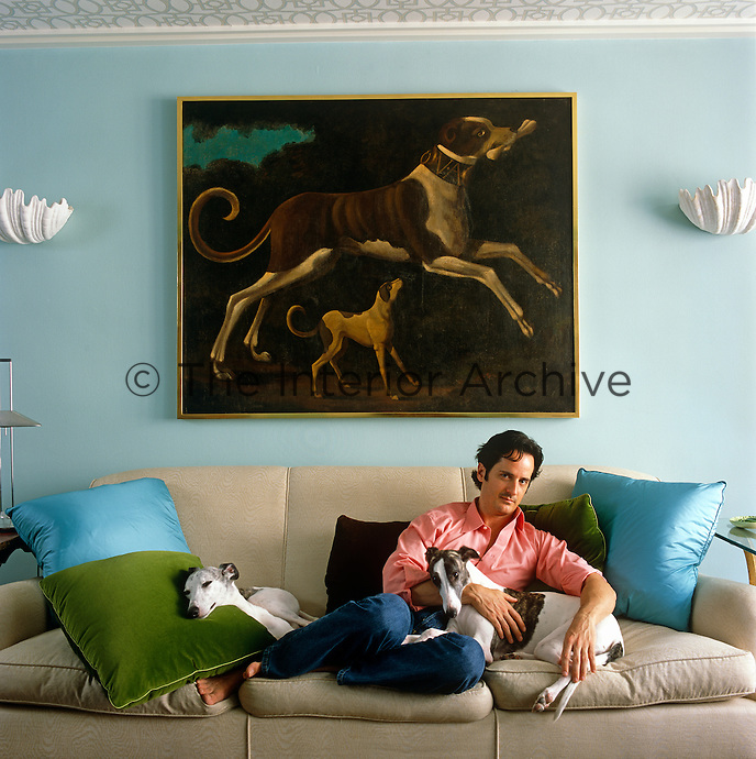 Portrait of the interior designer James Andrew with his two whippets Nigel and Rupert in the living room of his New York apartment