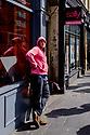 "Edinburgh, UK. 15.04.2017. Man in pink hoodie, outside pink-signed ""Sally"" salon services shop, Nicolson Street. Photograph © Jane Hobson."