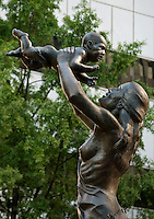 "This statue on Charlotte's Trade and Tryon streets Square is one of four standing on each corner of the intersection. The sculptures were created by artist Raymond Kaskey and are titled ""Transportation,"" ""Future,"" ""Commerce,"" and ""Industry."" This statue, Future, is symbolized by a woman holding a child."