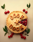 Cherry pie with Cook Book written on it in pastry