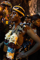 man participating in Thaipusam ceremonies at Batu Caves, Kuala Lumpur, Malaysia, 2012. Thaipusam ceremonies, celebrated by tamile Hindu community in Malaysia, take place  in Sanctuary of Batu Caves at the border of Kuala Lumpur, each year around end of January or beginning of February, according to Hindu moon calendar. The event is paying hommage to Lord Murugan, a spirit or god created by Shiva to lead the army of gods against the army of evil demons, finally defeating the evil spirits. There are many ways to present offerings or sacrifices for this major religious event. Devotees mortify their bodies by carrying heavy kavaris with spears fixed in their skin or fruits, flowers and little post with holy milk fixed with hooks in their skin, ascending the stairways to the sanctuary in trance, `followed by assistant  taking care and musicians playing loud and fast rhythmic trance music.  Many families shave their head in a ritual before ascending the stairways, as part of rituals to obtain salvation for their ancestors.