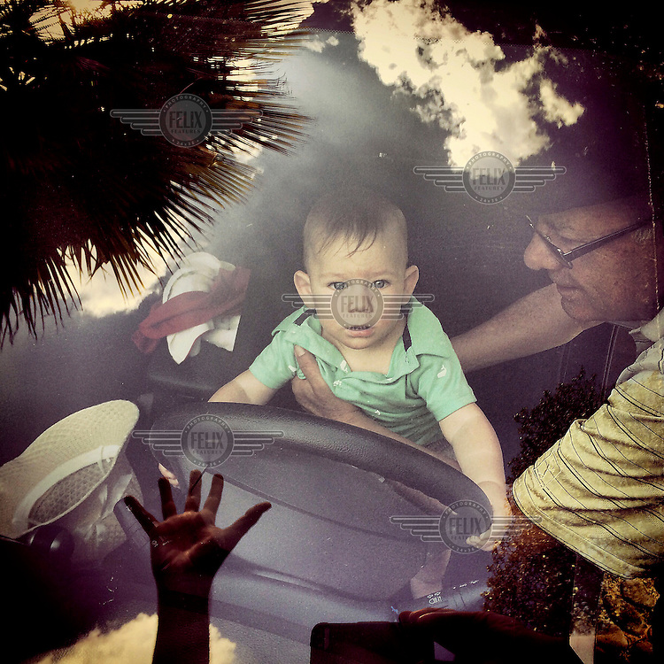 Victor Gachet plays with his grandson, Nahuel, in the front seat of a car.