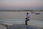 A man watches the moon rise over the Shatt al-Arab on Friday, October 22, 2010 in Basrah, Iraq.