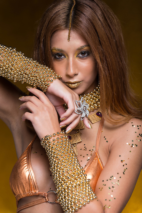 Beauty portrait of young caucasian woman with gold accesories.