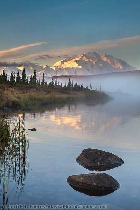 Rocks along the shore of Wonder lake as morning fog rises over the calm water at sunrise, Denali looms in the distance, Denali National park, Alaska.