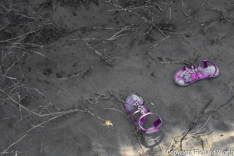 A pair of child size sandals left behind in the sand at Pomponio State Beach, California.