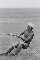 Male cowboy pulling lasso in field (B&W)