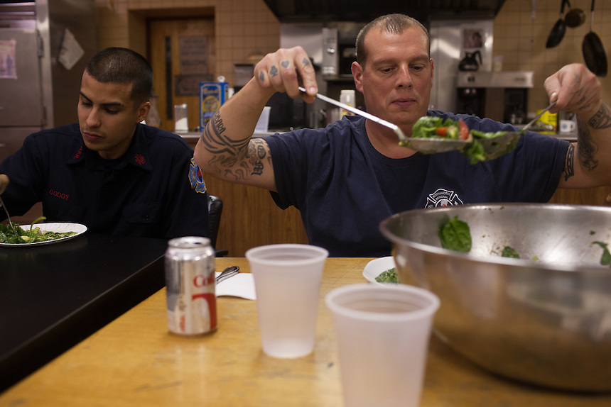 Probationary Fire fighter and veteran Andres Godoy eats dinner beside FF John Palombini at the 16th Street Fire House of the North Hudson Regional Fire and Rescue in Union City, NJ on November 07, 2013. Many vets say after the military they're still looking for a career with a sense of public service. Some vets have found that at the North Hudson Regional Fire and Rescue in New Jersey.