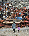 March 11, 2012, Rikuzentakata, Japan ? A mother and her daughter are dwarfed by the wall of debrise, remnants from the devastating earthquake and tsunami, in Rikuzentakata, Iuwate Prefecture, some 402 km northeat of Tokyo, on Sunday, March 11, 2012..Memorial ceremonies were held throughout Japan to mark the one year anniversary of the massive earthquake and tsunami that struck the country?fs northeastern region, killing just over 19,000 people and unleashing the world?fs worst nuclear crisis in a quarter century. The quake was the strongest recorded in the nation?fs history, and set off a tsunami that towered more than 65 feet in some spots along the northeastern coast, destroying thousands of homes and wreaking widespread destruction. (Photo by Natsuki Sakai/AFLO) AYF -mis-