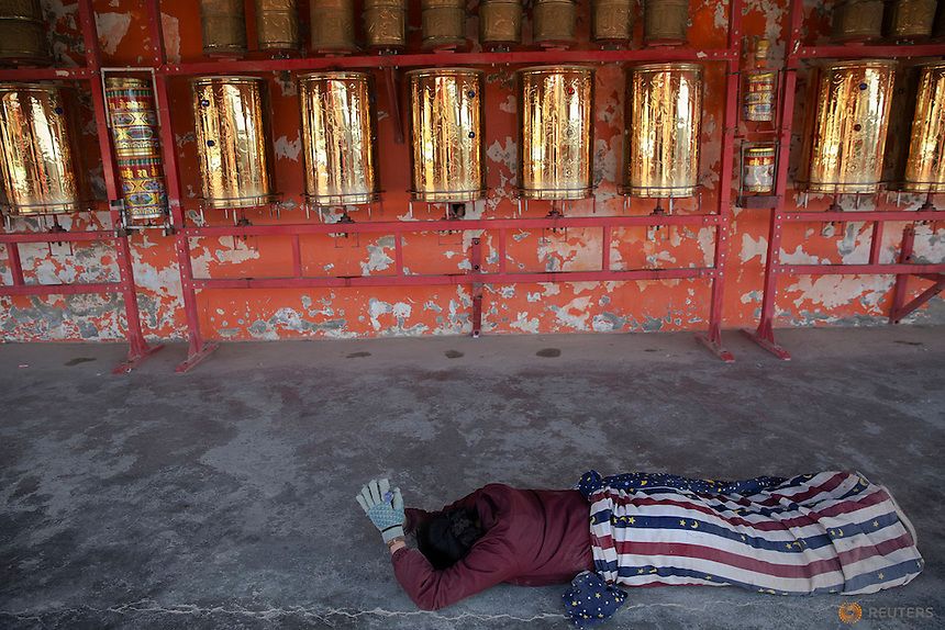 An ethnic Tibetan woman prostrates herself in front of prayer wheels as she circles around a monastery above the Larung Wuming Buddhist Institute, located some 3700 to 4000 metres above the sea level in remote Sertar county, Garze Tibetan Autonomous Prefecture, Sichuan province, China October 30, 2015. The Institute was founded in 1980 by Khenpo Jigme Phuntsok, an influential lama of Nyingma sect of Tibetan buddhism with only around 30 students but is now widely known as one of the biggest centres to study Tibetan Buddhism in the world. Today, tens of thousands monks and nuns live in small houses and log cabins surrounding the Larung Wuming Buddhist Institute. Picture taken November 1, 2015.   REUTERS/Damir Sagolj