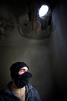 A Free Syrian Army soldier with a covered face stands in an abandoned building hit by shell fire in Zabadani, the only town in Syria officially held by the rebels. The hill town is surrounded by government forces. Protests against the ruling Baathist regime of Bashar al-Assad erupted in March 2011. Although they were initially peaceful,  they were violently repressed by the Syrian army and police. In response to being ordered to shoot unarmed civilians, large numbers of men deserted the army and formed the Free Syrian Army. The protest movement has now turned into an armed uprising with clashes between the regular army and the Free Syrian Army taking place in early 2012..