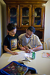 Dennis Sawyer, right, help his son Daniel, left, with his homework January 27, 2010 in Sacramento, Calif. The Sawyer family receives $540/month in CalWORKs assistance from the state of California. Dennis is currently unable to work while recovering from cancer, and Sophia hasn't been able to find work. Gov. Arnold Schwarzenegger has proposed eliminating the CalWORKs program in an effort to balance the state's budget. CREDIT: Max Whittaker for The Wall Street Journal.CABUDGET