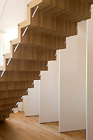 A flying staircase divides the open plan living area in front of the pivoting doors to the bedroom