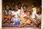 A group of young Fulani women and children in Ouagadougou, Burkina Faso eagerly crowd into the house for a photo. One of them dashes back outside, only to reappear moments later with a radio, which she proudly displays on her lap for all the world to see.